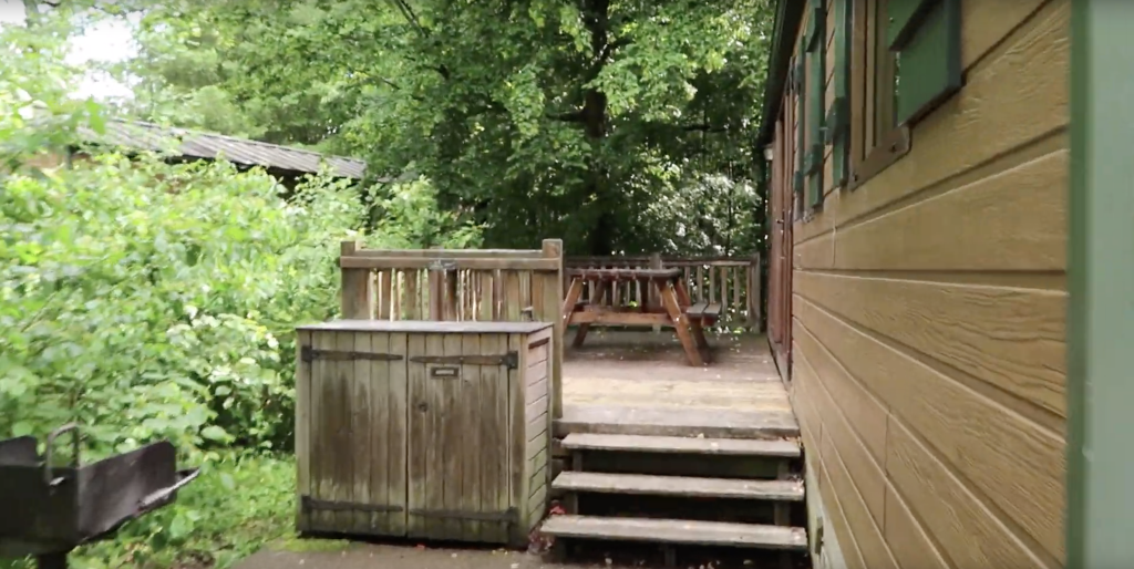 Outside of the Pioneer cabin with a deck, bbq and picknick table.